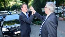 The Prime Minister David Cameron and Jean-Claude Juncker high five as they meet in Brussels