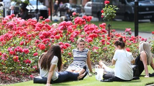 People enjoy the weather in Parliament Square, Leeds, as temperatures are tipped to soar to record levels