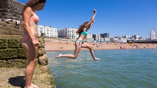 People jump off the sea defences into the water in Brighton, East Sussex as temperatures soar across the country.