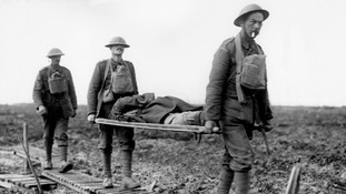 Two guardsmen bring in a wounded comrade on a stretcher at the First Battle of Passchendaele.