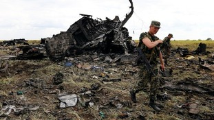 Pro-Russian separatists walk at the site of the crash of the II-76 army transport plane in Luhansk.