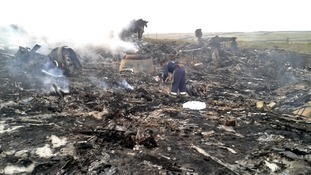 An Emergencies Ministry member works at the site of a Malaysia Airlines Boeing 777 plane crash