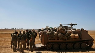 Israeli army reservists stand near an armoured vehicle in the Gaza strip.