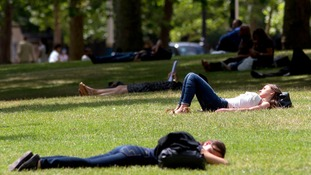 People enjoy the sunshine in St James Park