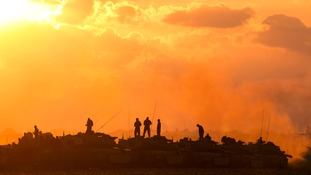 Israeli soldiers stand on top of their tanks and armoured personnel carriers (APCs) across from the northern Gaza.