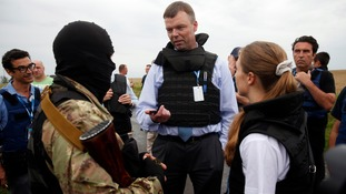 Organisation for Security and Cooperation in Europe (OSCE) monitors speak with a pro-Russian separatist