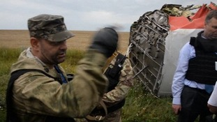 A pro-Russian militia member orders the OSCE monitors to leave the crash site.