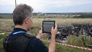 A monitor takes images of the crash site on his tablet.