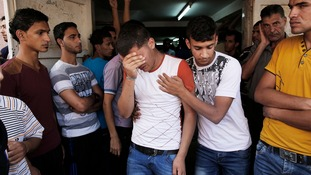A relative of Palestinians, who medics said were killed overnight by Israeli shelling, grieves at their funeral.