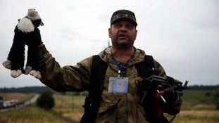 A pro-Russian separatist holds a cuddly toy from the wreckage.
