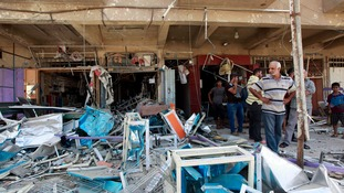 Locals inspect the damage after a bomb ripped through houses and shop premises.