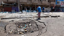 Civilians inspect a bomb site in the Jihad neighborhood in Baghdad.