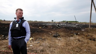 An inspector stands at the crash site of MH17 which has still not been cleared.