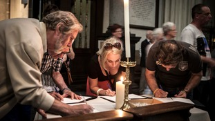 People sign a book of condolence at the cathedral.