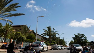 Israeli police and members of the media take cover as the Iron Dome intercepts Hamas rockets.