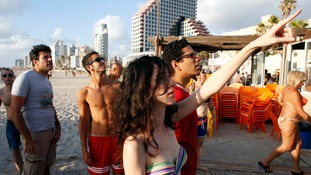 Tel Aviv beach-goers watch as a Hamas rocket is intercepted.