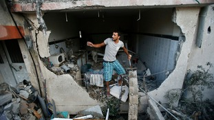 A Palestinian man inspects a house in Gaza City which police said was damaged in an Israeli air strike.