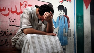 A man holds his head at a UN school where people sought refuge during heavy shelling.