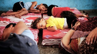 Palestinian children sleep at the school after seeking refuge from shelling.