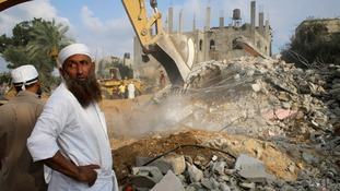 A bulldozer searches for victims amongst the rubble of a house in Khan Younis, in the southern Gaza Strip.