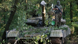 A pro-Russian separatist battalion poses for a picture atop a T-64 tank in Donetsk.