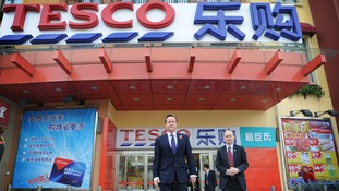 David Cameron visiting a Tesco in China, a market that has proven difficult for the company.