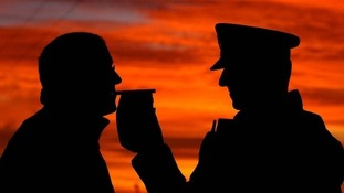 Silhouette of policeman breathalising a man
