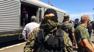 A militia member stands by as an inspection of the train is carried out.