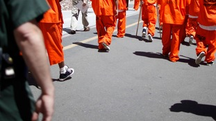 Prisoners in orange jumpsuits.