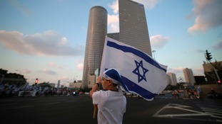 An Israeli boy holds a flag during a protest in Tel Aviv, i