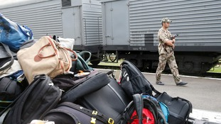 An armed pro-Russian separatist stands guard near the train transporting the remains of victims