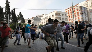 Palestinians take cover as warning Israeli air strikes are fired at a nearby building in Gaza City.