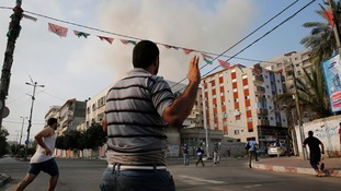 Palestinians react after warning Israeli air strikes hit a building in Gaza City.