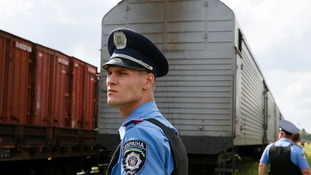 A Ukrainian policeman watches as a train carrying the victims of downed flight MH17 arrives in Kharkiv.