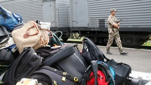 A pro-Russian separatist stands near the train transporting the victims of the flight MH17 crash as their luggage is seen in the foreground.