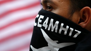 A man wearing a face mask attends a demonstration outside the Ukrainian embassy in Kuala Lumpur.