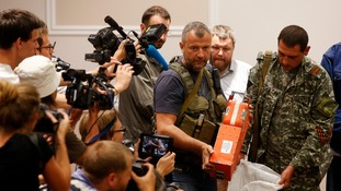A pro-Russian separatist shows members of the media a black box belonging to Malaysia Airlines flight MH17.