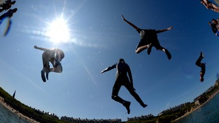 Visitors at Cullercoats, North Tyneside, jump in the water as temperatures reach the high 20s.