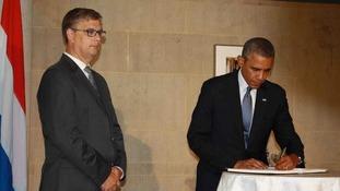 Barack Obama signing a book of condolence.