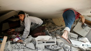 Palestinian boys go through the rubble of their destroyed home in Gaza.