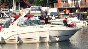 Boat with people searching for boy on River Thames