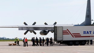 Officials carry coffins from a refrigerated lorry at Kharkiv airport.