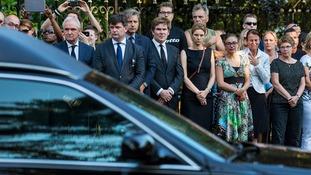 Devastated family members of victims look on as the hearses arrive at the Korporaal van Oudheusden barracks.