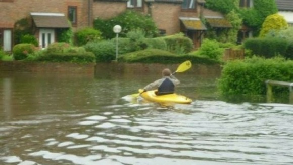 A canoeist makes best use of the conditions in Chaffer Lane, Birdham, West Sussex.