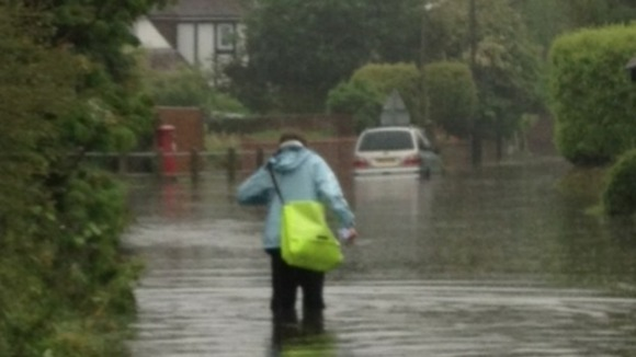 Paperboy Luke Wayne battles his way through severe flooding in Limmer Lane, Felpham to do his round.