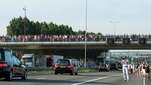 People line the roadside