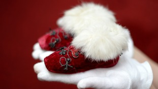 A pair of red velvet fur lined boots worn in the 1840s by Prince Albert Edward, later King Edward VII, when he was a baby.