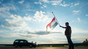 A Netherlands flag flying at half-mast as a hearse carrying victims passes.
