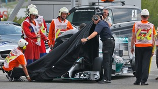 Track marshals and Mercedes crew members cover Lewis Hamilton's car.