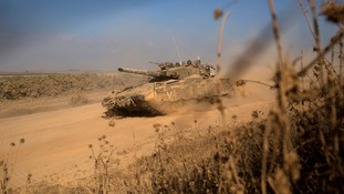 Israeli soldiers ride on top of a tank as the Gaza offensive continues.